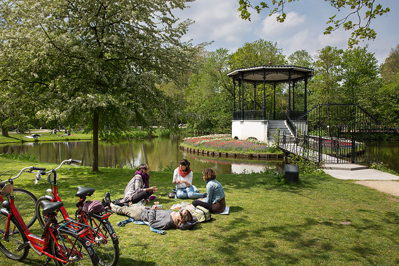 Young people sitting in Vondelpark with bikes